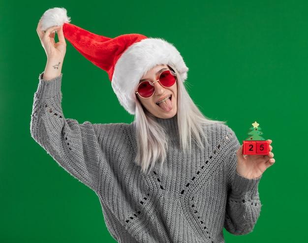 Jonge blonde vrouw in winter trui en kerstmuts met rode bril met speelgoed blokjes met kerstdatum plezier tong uitsteekt staande over groene achtergrond Gratis Foto
