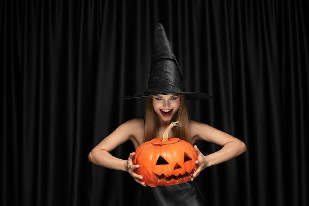 Jonge blonde vrouw in zwarte hoed en kostuum op zwart Gratis Foto