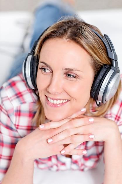 Jonge blonde vrouw luisteren muziek met een koptelefoon Gratis Foto