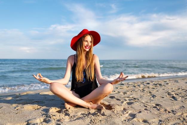 Jonge blonde vrouw mediteren in de buurt van oceaan, bonenvakantie, zonneschijn, het dragen van rode hoed en balktop, gezonde levensstijl, yogastemming. zittend op zand en genieten van vakantie. Gratis Foto
