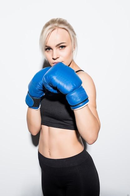 Jonge blonde vrouw met blauwe bokshandschoenen bereid om op wit te vechten Gratis Foto