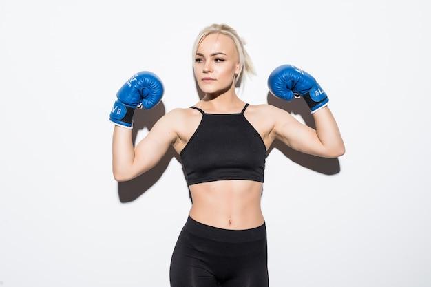 Jonge blonde vrouw met blauwe bokshandschoenen op wit Gratis Foto