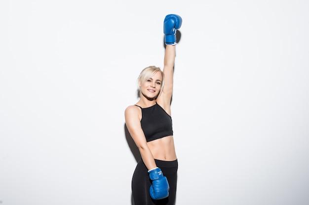 Jonge blonde vrouw met blauwe bokshandschoenen op witte overwinning hand omhoog Gratis Foto