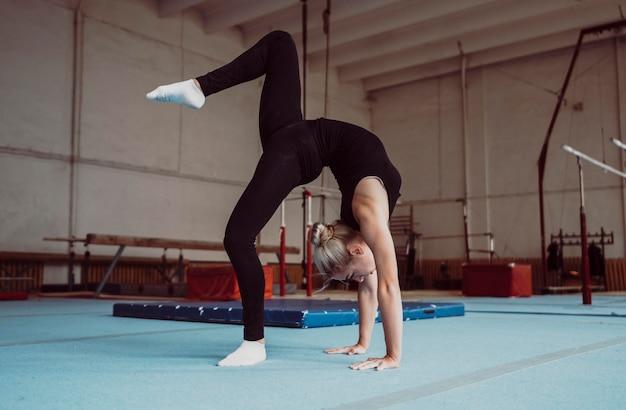 Jonge blonde vrouw opleiding voor olympische gymnastiek Premium Foto