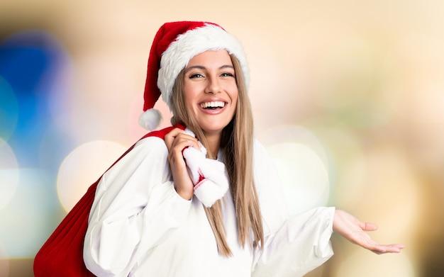 Jonge blonde vrouw oppakken van een zak vol cadeautjes in kerstvakantie Premium Foto