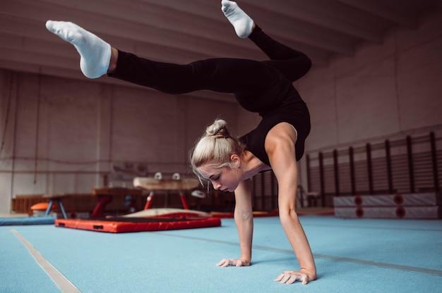 Jonge blonde vrouw training voor kampioenschap turnen Gratis Foto