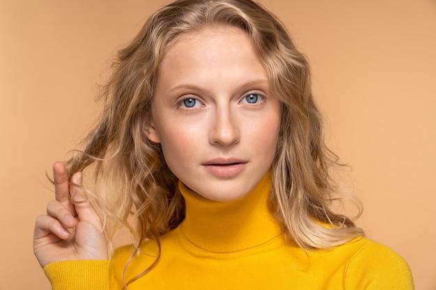 Jonge blonde vrouw wat betreft haar natuurlijk zacht krullend haar Premium Foto
