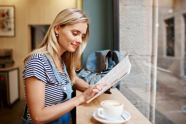Jonge blonde vrouw zitten in café en lezen Gratis Foto