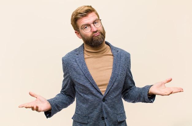Jonge blonde zakenman die zich in verwarring gebracht en verward voelt, onzeker over het juiste antwoord of besluit, in een poging een keuze te maken Premium Foto