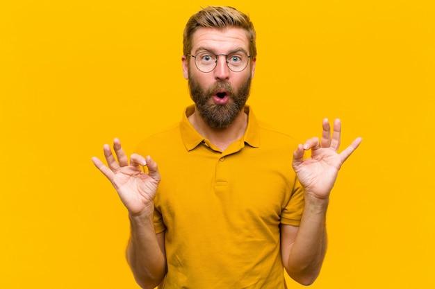 Jonge blondemens die geschokt, verbaasd en verrast voelen, goedkeuring tonen die ok teken met beide handen oranje muur maken Premium Foto