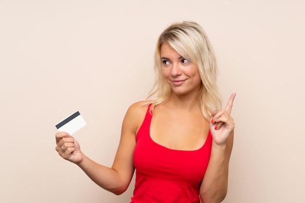 Jonge blondevrouw die een creditcard houden Premium Foto