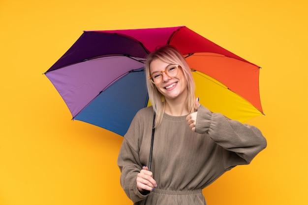 Jonge blondevrouw die een paraplu over het geïsoleerde gele muur geven houden duimen op gebaar Premium Foto