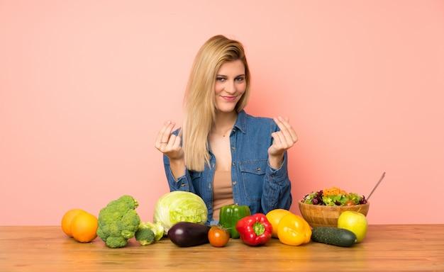 Jonge blondevrouw die met vele groenten geldgebaar maken Premium Foto