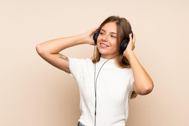 Jonge blondevrouw die mobiel met hoofdtelefoons gebruiken Premium Foto