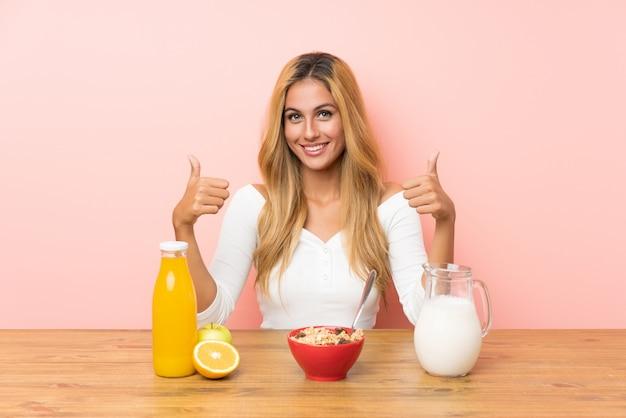 Jonge blondevrouw die ontbijtmelk geven hebben duimen op gebaar Premium Foto