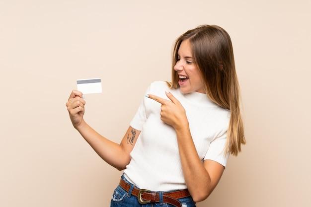 Jonge blondevrouw die over geïsoleerde muur een creditcard houden Premium Foto