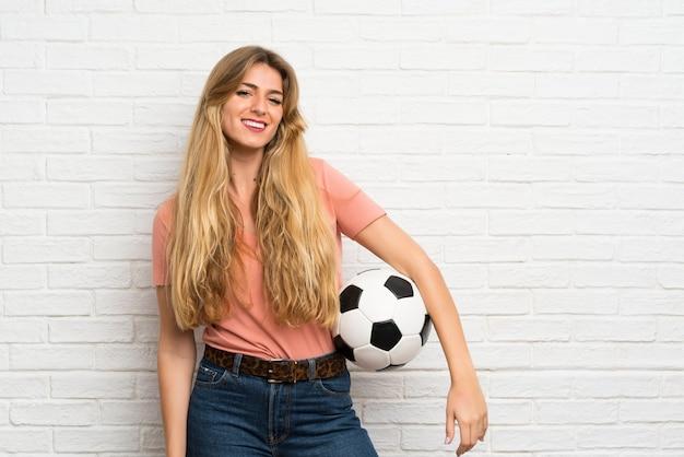 Jonge blondevrouw die over witte bakstenen muur een voetbalbal houden Premium Foto