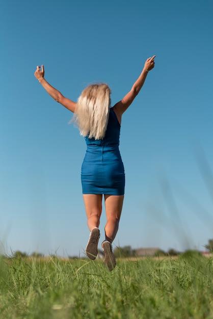 Jonge blondevrouw die terwijl het houden van wapens in de lucht springt Gratis Foto