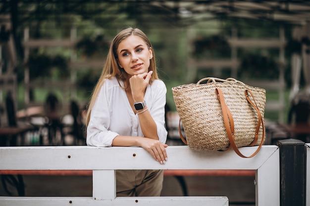 Jonge blondevrouw die zich door omheining in park bevinden Gratis Foto