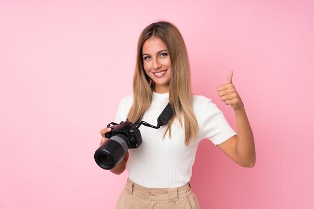 Jonge blondevrouw met een professionele camera en met omhoog duim Premium Foto