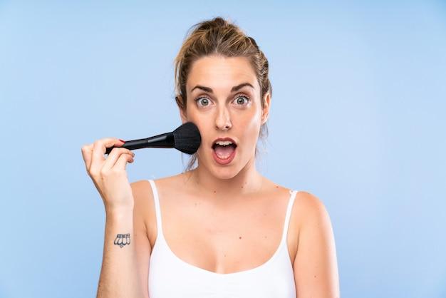 Jonge blondevrouw met make-upborstel die verrassingsgebaar doen Premium Foto