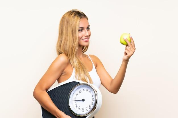Jonge blondevrouw met weegmachine en met een appel Premium Foto