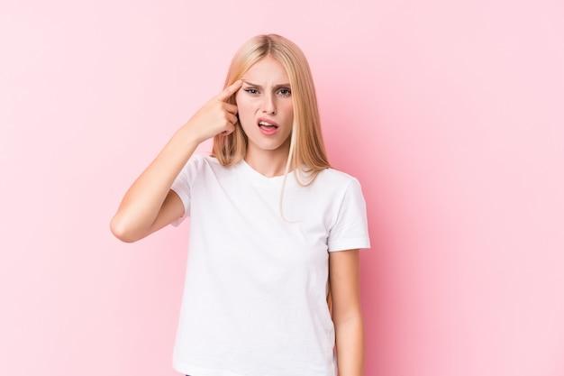 Jonge blondevrouw op roze muur die een teleurstellingsgebaar met wijsvinger tonen. Premium Foto