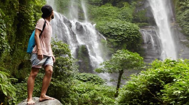 Jonge blootvoetse toerist in honkbal glb die zich op grote steen bevinden en terug naar waterval achter hem in mooie exotische aard kijken. bebaarde reiziger genieten van dieren in het wild tijdens het wandelen in het regenwoud Gratis Foto