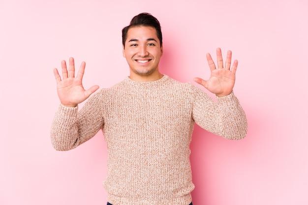 Jonge bochtige man poseren in een roze muur geïsoleerd met nummer tien met handen. Premium Foto