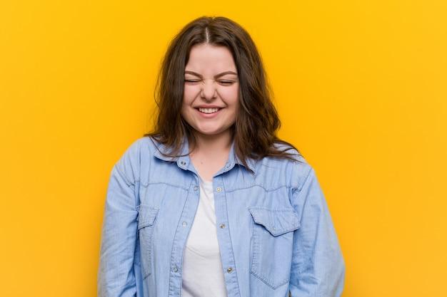 Jonge bochtige plus size vrouw lacht en sluit de ogen, voelt zich ontspannen en gelukkig. Premium Foto