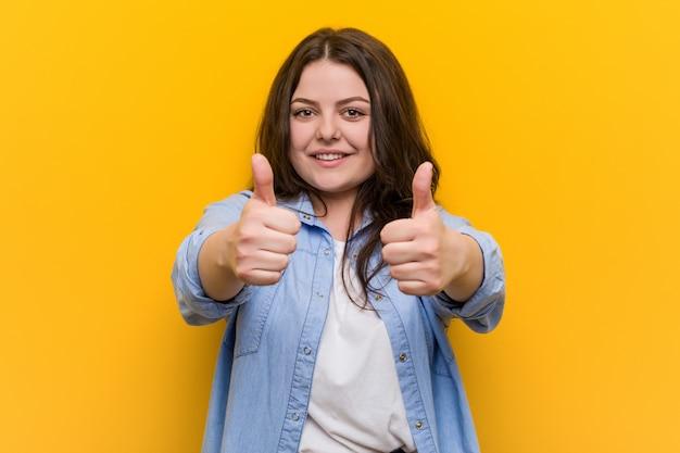 Jonge bochtige plus size vrouw met duimen omhoog, proost over iets, steun en respect. Premium Foto