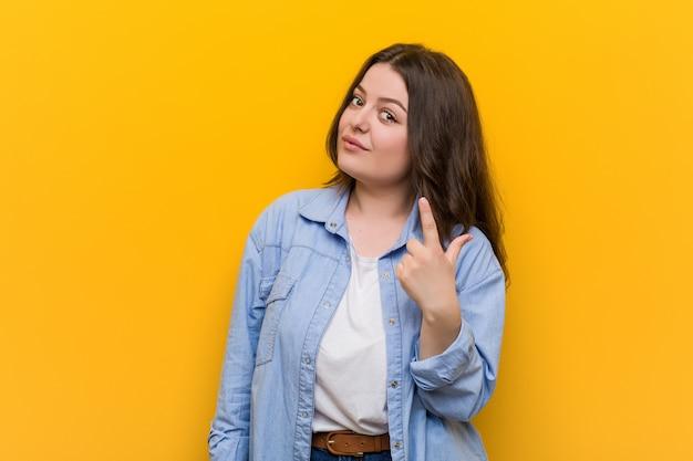 Jonge bochtige plus size woman wijzend met de vinger naar je alsof uitnodigen dichterbij komen. Premium Foto