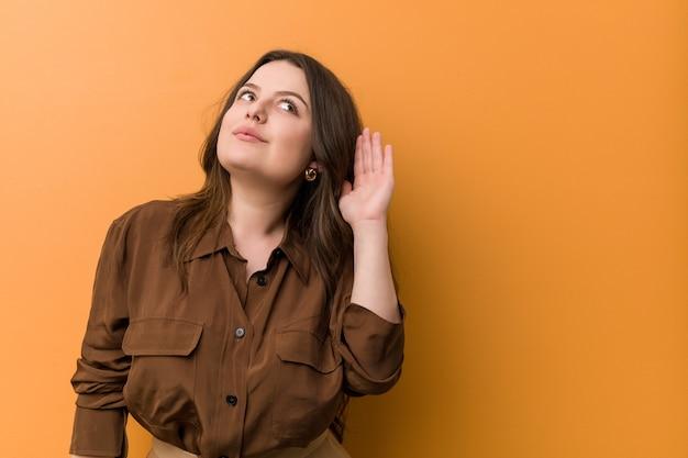 Jonge bochtige russische vrouw die aan het luisteren van een roddel probeert. Premium Foto