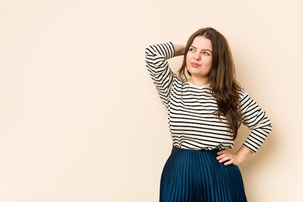 Jonge bochtige vrouw aanraken van het hoofd, denken en een keuze maken. Premium Foto
