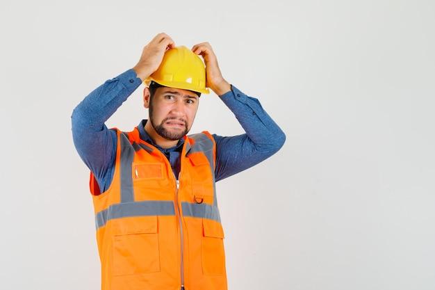 Jonge bouwer hand in hand op het hoofd in shirt, vest, helm en op zoek naar hulpeloos, vooraanzicht. Gratis Foto