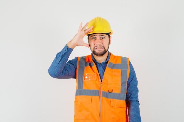 Jonge bouwer in overhemd, vest, helm die hand boven het hoofd houdt en treurig, vooraanzicht kijkt. Gratis Foto
