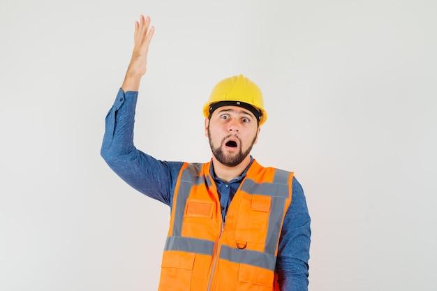Jonge bouwer in overhemd, vest, helm die hand opheft en geschokt, vooraanzicht kijkt. Gratis Foto
