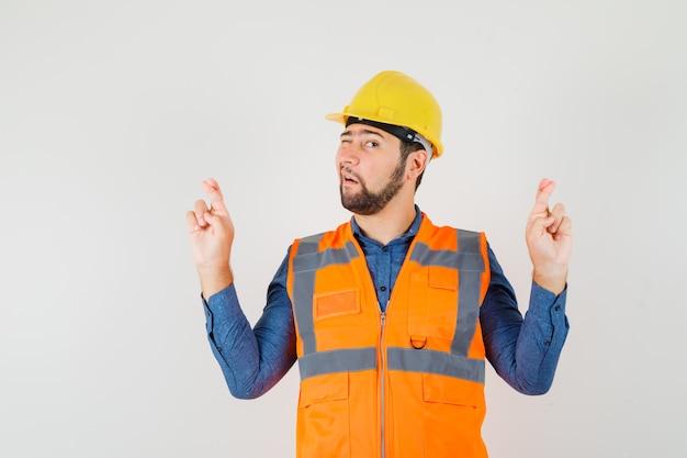 Jonge bouwer in overhemd, vest, helm die vingers gekruist houden en oog knipogen, vooraanzicht. Gratis Foto