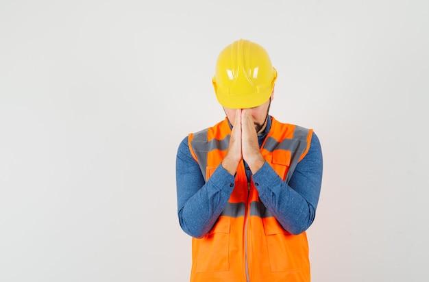 Jonge bouwer in shirt, vest, helm hand in hand in gebed gebaar en op zoek kalm, vooraanzicht. Gratis Foto