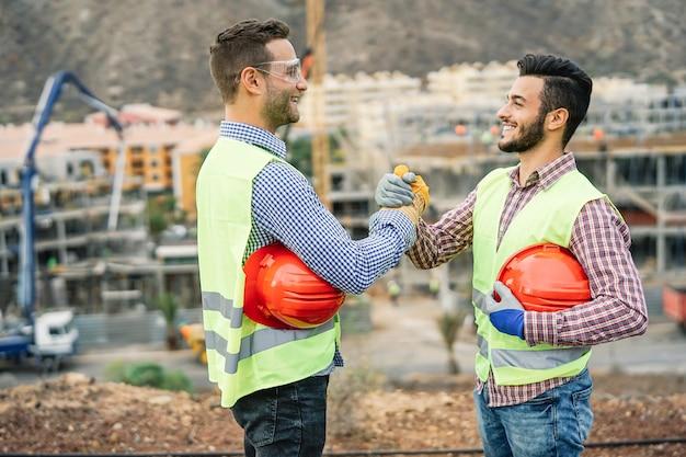 Jonge bouwers die handen schudden die een overeenkomst over bouwwerf maken Premium Foto