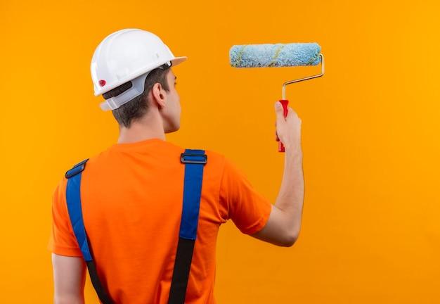 Jonge bouwersmens die bouwuniform en veiligheidshelm dragen schildert de muur met een rolborstel Gratis Foto