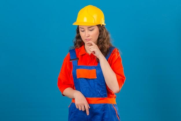 Jonge bouwersvrouw in eenvormige bouw en veiligheidshelm die zich met hand op kin bevindt die onderaan denkend hebbend over geïsoleerde blauwe muur kijkt Gratis Foto
