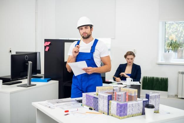 Jonge bouwsupervisor die aantekeningen maakt op kantoor Premium Foto