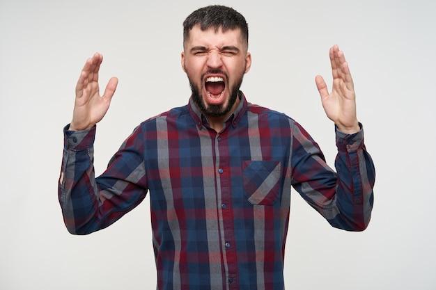 Jonge boze brunette man met baard emotioneel verhogen van zijn handen en hevig schreeuwen met gesloten ogen, geïsoleerd over witte muur Gratis Foto