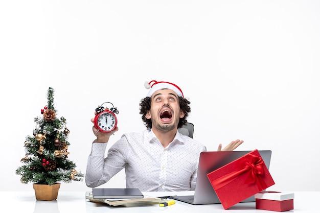 Jonge boze zakenman met kerstman hoed en klok te houden en zittend in het kantoor op donkere achtergrond Gratis Foto