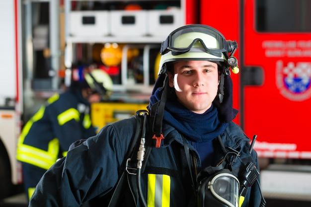 Jonge brandweerman in uniform voor brandweerwagen Premium Foto