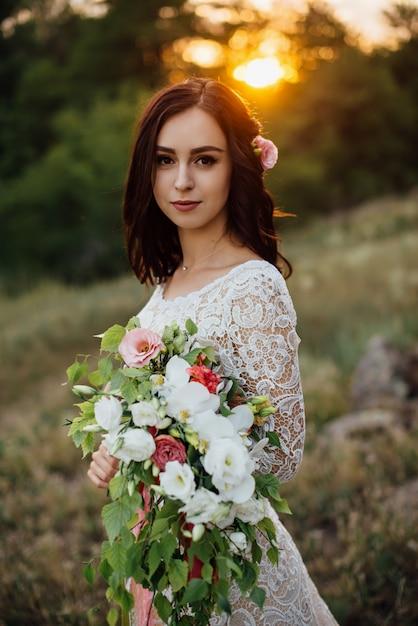 Jonge bruid buiten op een zomer weide bij de zonsondergang Premium Foto