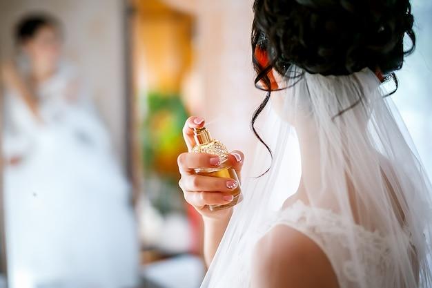 Jonge bruid gebruikt haar dure parfum Premium Foto