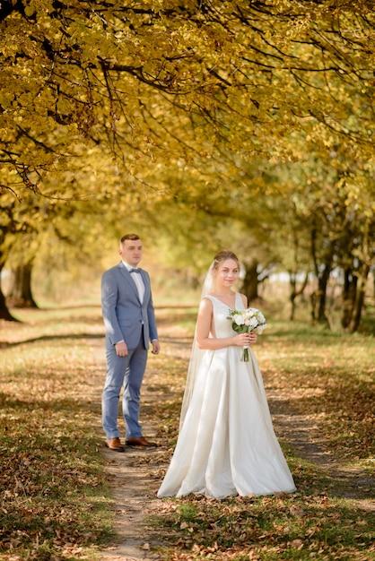 Jonge bruidegom en mooie bruid in de herfst park. focus op het meisje. het meisje blaast een bruidsboeket in haar handen. Premium Foto