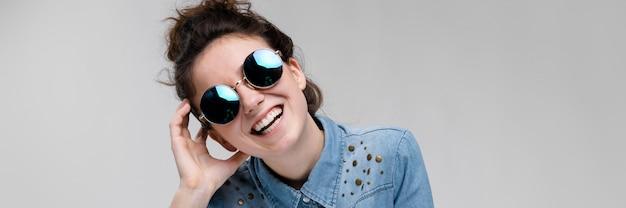 Jonge brunette meid in ronde glazen. haren zijn verzameld in een knot. het meisje legde haar hand op haar hoofd. Premium Foto
